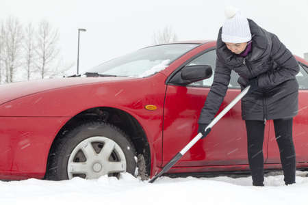 Cute female driver shovelling and removing snow from his car during a snow storm Stock Photo