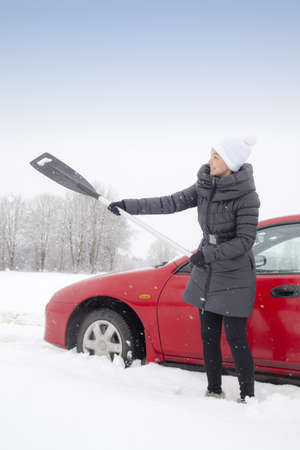 Cute female driver shovelling and removing snow from his car during a snow storm photo