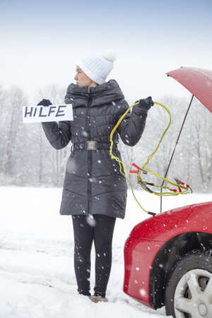 boost: Cute girl waiting for help on the road holding HELP sign, she needs a battery boost for her car, on very cold, snowy winter day