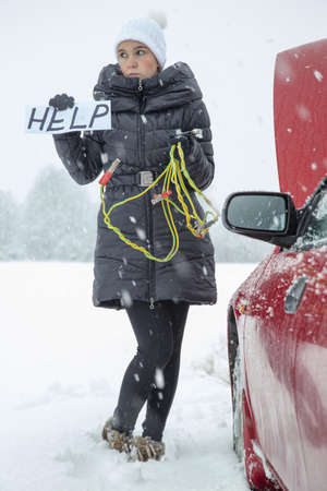Cute girl waiting for help on the road holding HELP sign, she needs a battery boost for her car, on very cold, snowy winter day