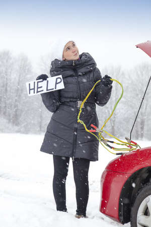 Cute girl waiting for help on the road holding HELP sign, she needs a battery boost for her car, on very cold, snowy winter day photo