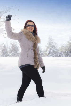 Mid aged cute smiling woman waving hello outdoors on winter day photo