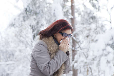 Portrait of a cute mid aged woman blowing nose-sneezing,\ outdoors on winter day