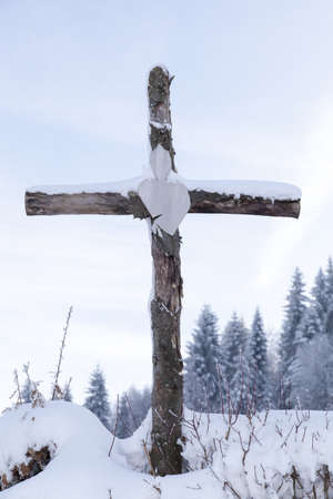 Wooden Station of the Cross in snowy forrest, against morning sun photo