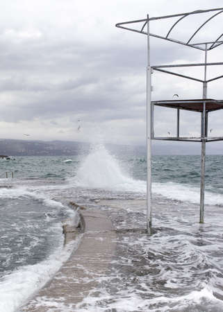 baywatch: Big wave on stormy day, beating on the seaside resort coast with abandoned baywatch- beach life guard tower