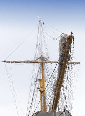 Front view of vintage sailing ship mast and sails against sky photo