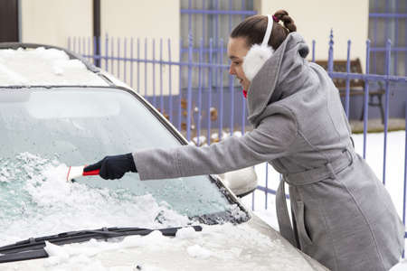 Smiling cute woman removing ice from the car windshield photo