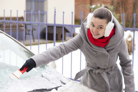 Smiling cute woman removing snow from car windshield