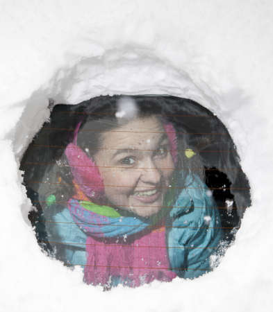 Cute smiling girl looking  through a hole in a snowy car window photo