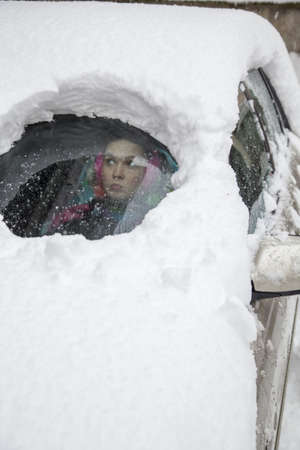 snowstorm: Young  woman driver looking from behind a very foggy and snowy car window  Stock Photo