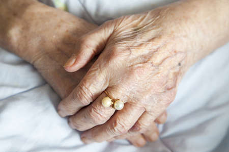 golden years series: Series of photos  Hands of 92 years old lady with beautiful golden ring with pearls - close up selective focus