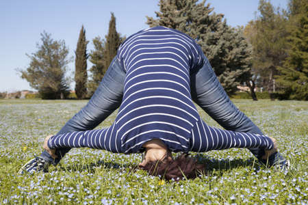 Mid aged woman doing yoga streching exercises outside in the garden  Stock Photo