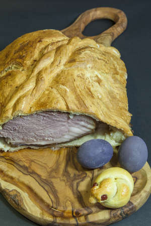 Delicious ham baked in bread dough with easter decoration, on olive tree plate,  Easter eggs are colored in superior red wine Teran,  series of Easter baked ham,    photo