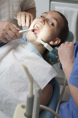 Frightened girl having her teeth checked by doctor