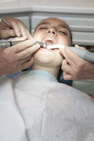 Frightened girl having her teeth checked by doctor photo