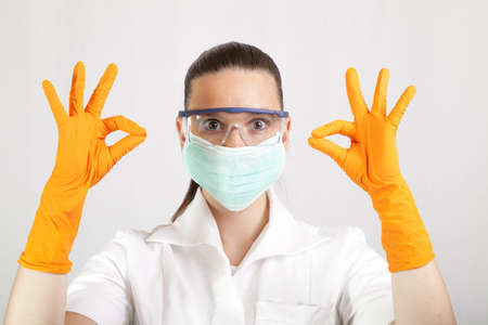 Cute female doctor surgeon or chemist wearing latex gloves, showing OK sign photo