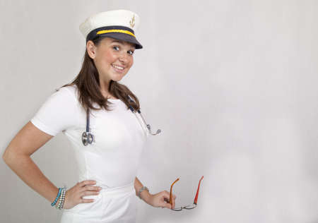 Cute smiling female doctor in captain cap, leader of medical crew on big luxury cruiser  photo