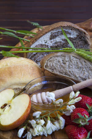 Fresh baked bread and acacia honey in glass bowl with wooden drizzler, served on olive tree plate with bio Topaz apple, selective focus photo