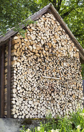 Accurately combined fire wood at a wooden house wall photo