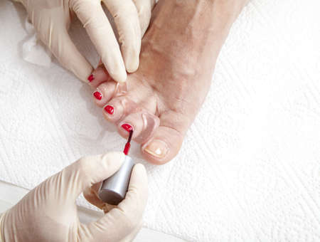 Close up of a beautician preparing and applying a nail polish to a client feet photo