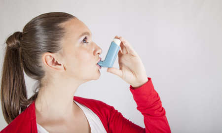 Cute girl using an asthma inhaler for preventing attacks, space for Your text