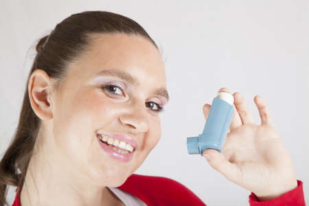 Cute smiling girl using an asthma inhaler for preventing attacks, space for Your text   photo