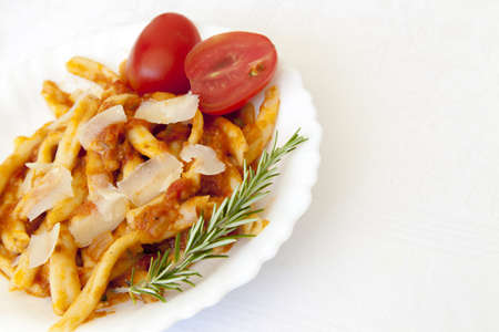 Delicius hand made pasta with sauce and parmesan cheese, served on white ceramic plate and decorated with organic tomatoes and rosemery, space for text photo