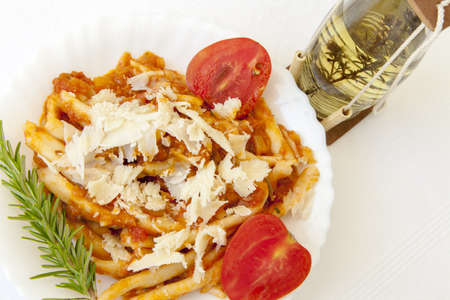 rakia: Delicius hand made pasta with sauce and parmesan cheese, served on white ceramic plate and decorated with organic tomatoes, rosemery and Travarica rakia, selective focus