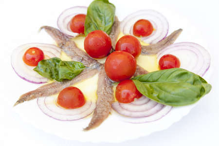 Sardine fillets on a white ceramic plate, served with various organic vegetables and decorated with  Mediterranean herbs, basil photo
