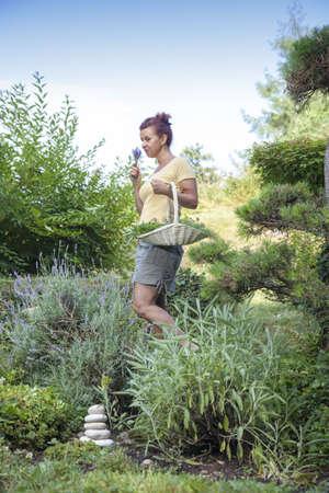 Cute female gardener surrounded with fresh organic herbs posing in beautiful feng shui garden