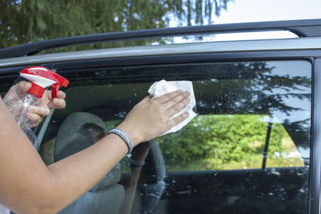 Cute young woman cleaning car window with white recicled paper towel, space for text photo