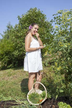 Cute young female gardener tasting fresh picked cherry tomato in her beautiful organic garden  photo