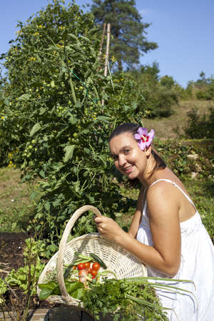 Cute young female gardener surrounded with fresh picked plants posing in beautiful organic garden photo