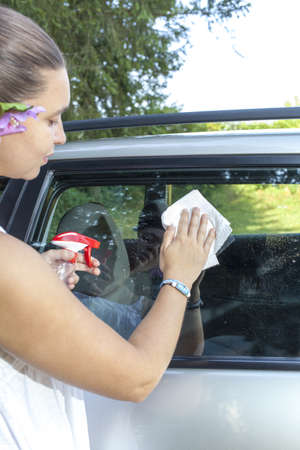 Cute young woman cleaning car window with white recicled paper towel photo