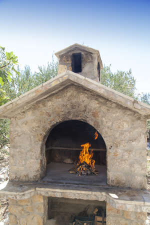 Fire in traditional rich bbq fireplace, made from stone brics  photo
