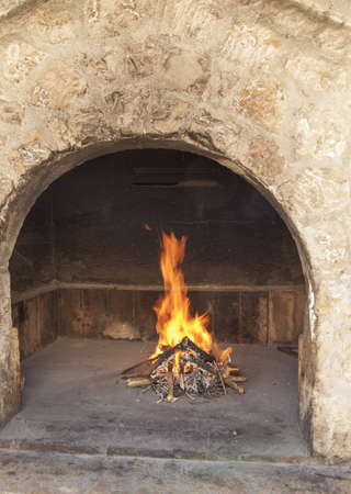 stone  fireplace: Fire in traditional rich bbq fireplace, made from stone brics