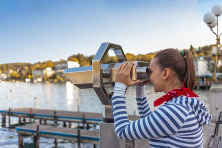 Young cute woman looking through a coin operated binoculars photo