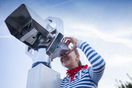 Young smiling woman using coin operated binoculars, against blue sky photo