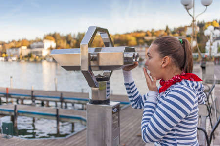 operated: Young surprised woman using coin operated binoculars