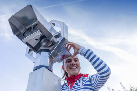 operated: Young smiling woman using coin operated binoculars, against blue sky
