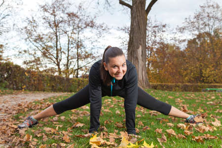 Young, beautiful woman stretching in the park in autumn leaves photo