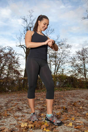 Runner woman checking  time and her pulse rate on sport watch, after running in city forest park, in fall
