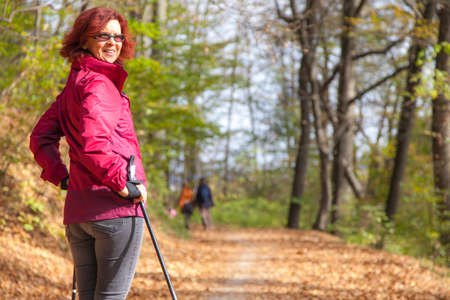 nordic walking: Sportive cute mid aged female hiker Nordic walking cross country under the blue sky of the morning sun in the autumn forest