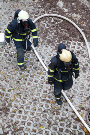 hosepipe: Professional firefighters rush to rescue injured people  Stock Photo