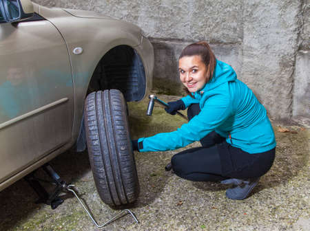 Young smiling woman changes car tyres photo