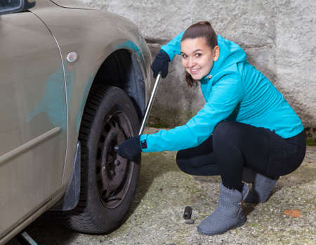 screw jack: Cute young woman driver loosening nuts on a vehicle wheel for a tire change
