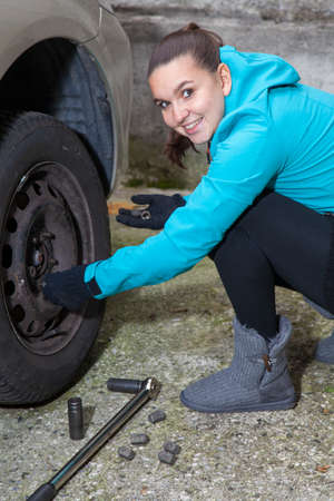 replacing: Pretty girl replacing summer tyres with winter tyres, before coming winter, Stock Photo