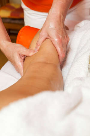 Woman receiving a leg and foot massage and lymphatic drainage while lying on a towel in a awarded health massage center,  series of various techniques  photo
