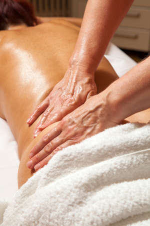 Woman receiving a professional therapeutic massage and lymphatic drainage while lying on a towel in a awarded health massage center,  series of various techniques  photo