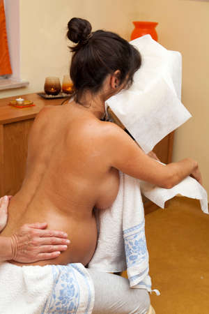 Pregnant young latina woman sitting on a massage chair and receiving a relaxing prenatal massage, various techniques